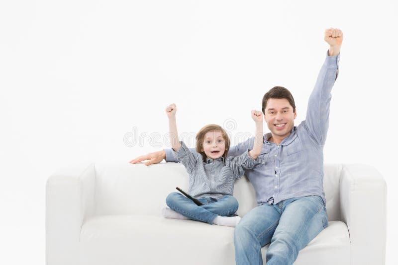 Esportes de observação de sorriso do homem e do filho na tevê e na equipe de apoio em casa fotografia de stock