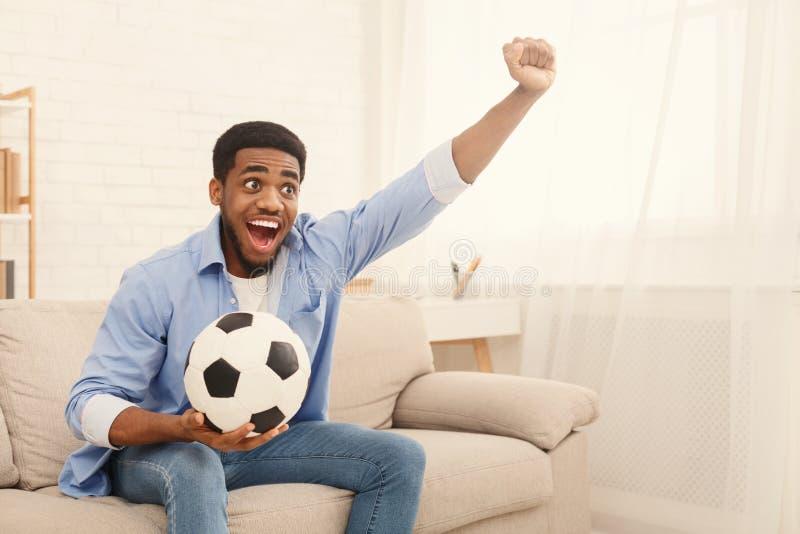 Esportes de observação entusiasmados do indivíduo preto na tevê em casa imagem de stock
