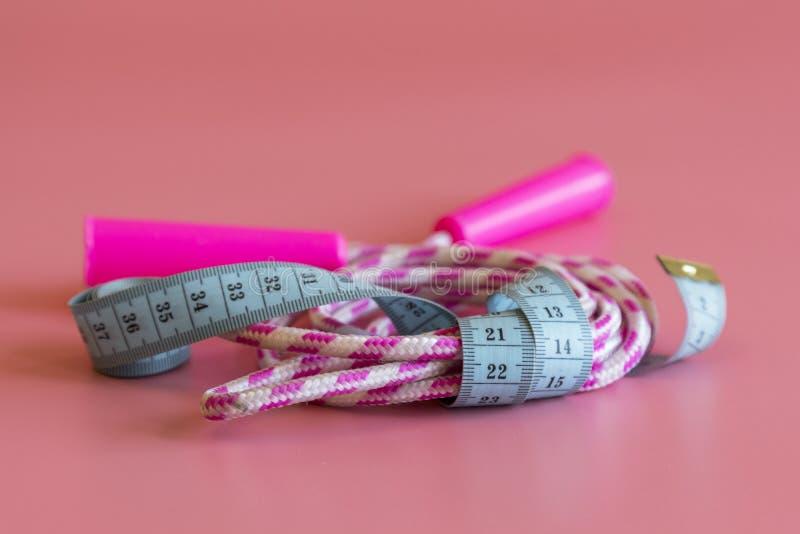 Esportes e ideia da saúde Conceito do exercício e do rafrescamento Fita em torno da corda de salto e barbells na esteira da ioga  foto de stock