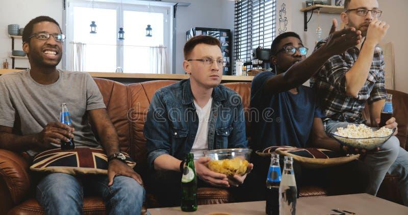 Esportes masculinos afro-americanos do relógio dos amigos na tevê Multi fãs geeky étnicos concentrados e sérios no sofá com pipoc imagens de stock