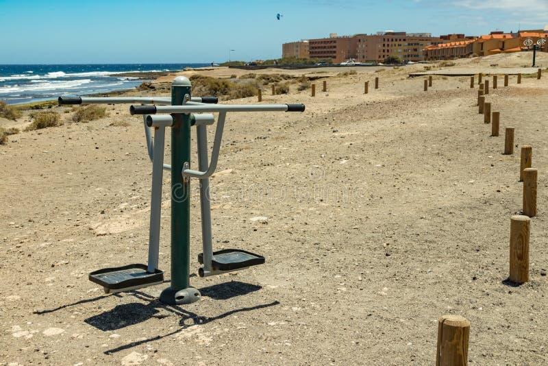 Esportes moídos ao longo da costa com o equipamento diferente da ginástica Dia ensolarado morno e ressaca delicada do mar Ostenta foto de stock royalty free