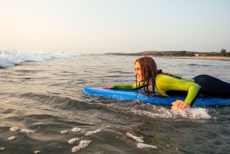 Esportiva linda mulher num traje de mergulho deitado num surfboard esperando por uma onda grande surf Girl in a wetcase surfing i imagens de stock royalty free