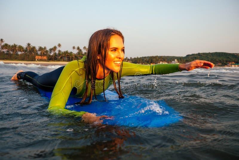 Esportiva linda mulher num traje de mergulho deitado num surfboard esperando por uma onda grande surf Girl in a wetcase surfing i fotografia de stock