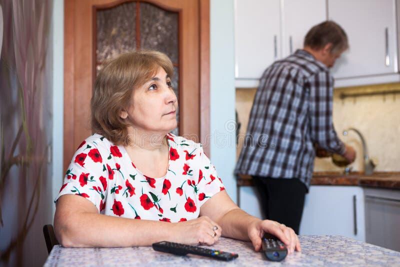 A esposa caucasiano olha a tevê e os restos, marido ajudam na cozinha - pratos das lavagens fotos de stock royalty free
