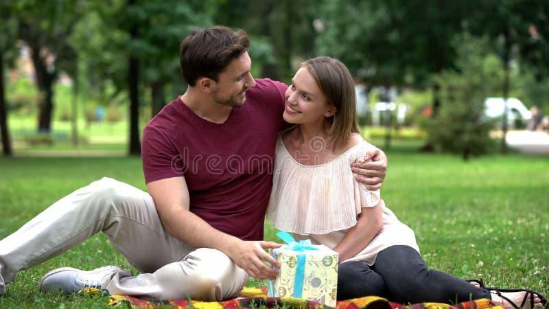 A esposa dá o presente ao marido amado, à celebração do aniversário ou ao aniversário fotos de stock
