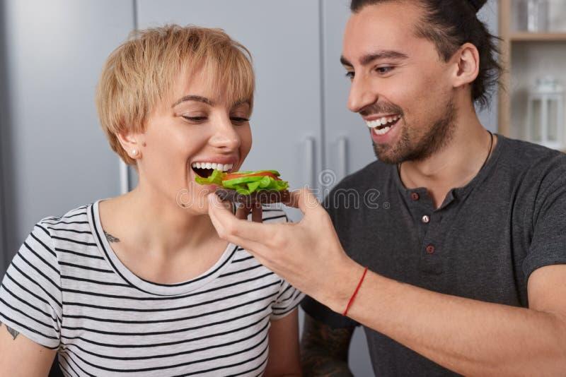 Esposa de alimentaci?n del hombre con el bocadillo por ma?ana fotografía de archivo