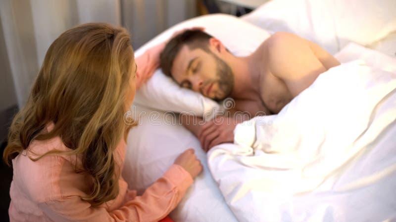 Esposa de inquietação que afaga seu cabelo do marido quando adormecido, recém-casados, oferecer o amor imagem de stock