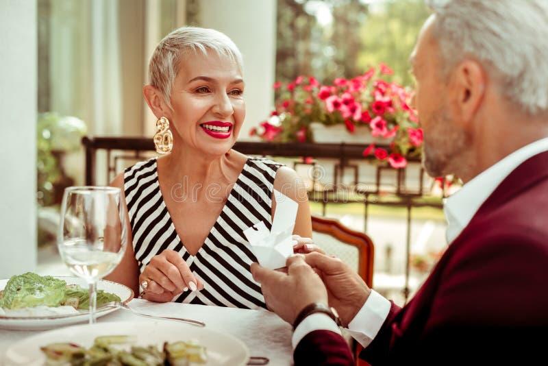 Esposa de irradiação de amor que sente grata ao receber o presente do marido imagens de stock royalty free
