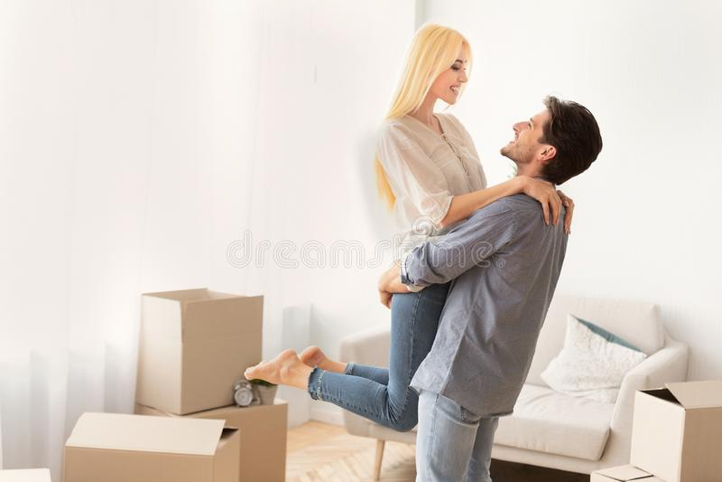 Esposa de levantamento de amor do marido entre caixas móveis no apartamento novo fotos de stock