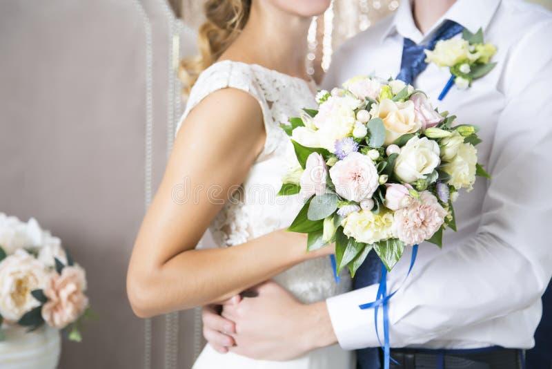 A esposa do marido abraça um ramalhete do casamento newlyweds Dia do casamento imagens de stock