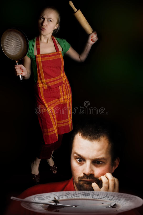 Esposa irritada com ferramentas da cozinha e o marido com fome imagens de stock royalty free