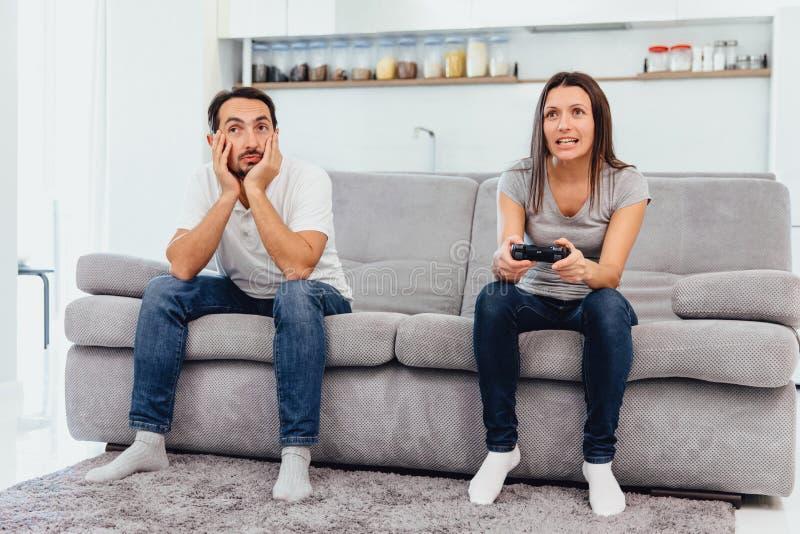 A esposa joga o jogo quando o homem apenas se sentar fotos de stock