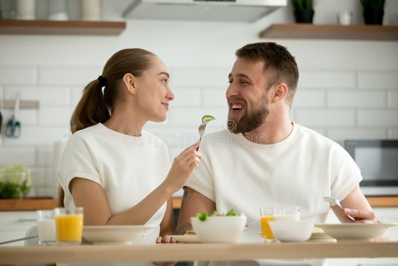 Esposa joven cariñosa que alimenta al marido barbudo durante el desayuno en ho imagenes de archivo