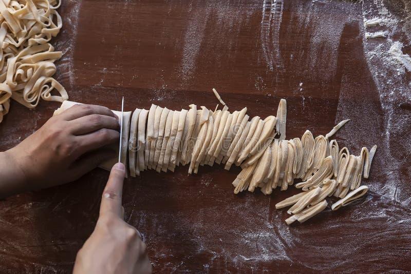 Esposa joven de la casa que prepara las pastas hechas en casa en la cocina Raya larga de la pasta del corte de la mujer para coci imagen de archivo