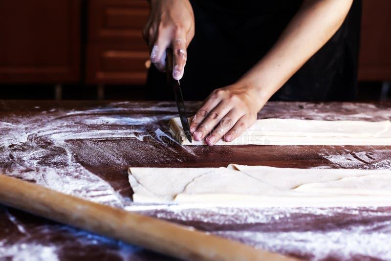 Esposa joven de la casa que prepara las pastas hechas en casa en la cocina Raya larga de la pasta del corte de la mujer para coci foto de archivo