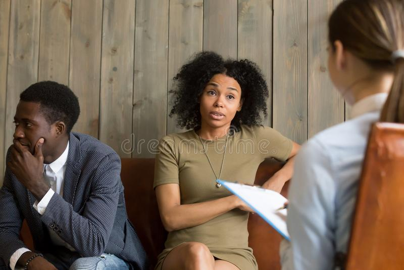 Esposa negra trastornada que discute problemas de la familia durante sessi de la terapia imagen de archivo