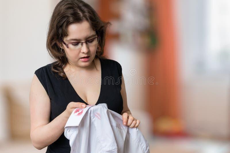 A esposa nova da inveja encontrou manchas vermelhas do batom na camisa branca de seu marido infiel fotografia de stock royalty free