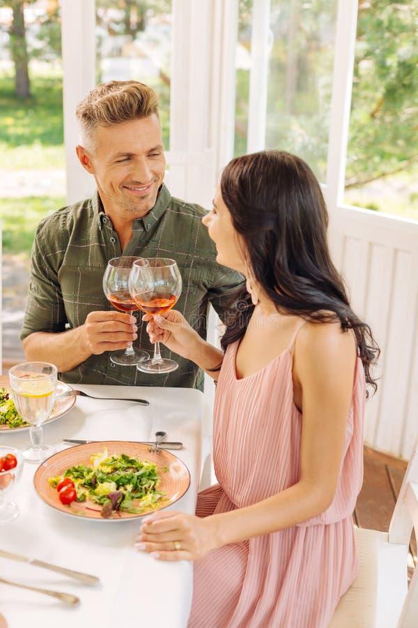 esposa Oscuro-cabelluda que lleva el vino de consumición del vestido rosado con el marido fotos de archivo