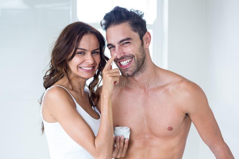 Esposa que aplica o creme na cara do marido em casa imagem de stock