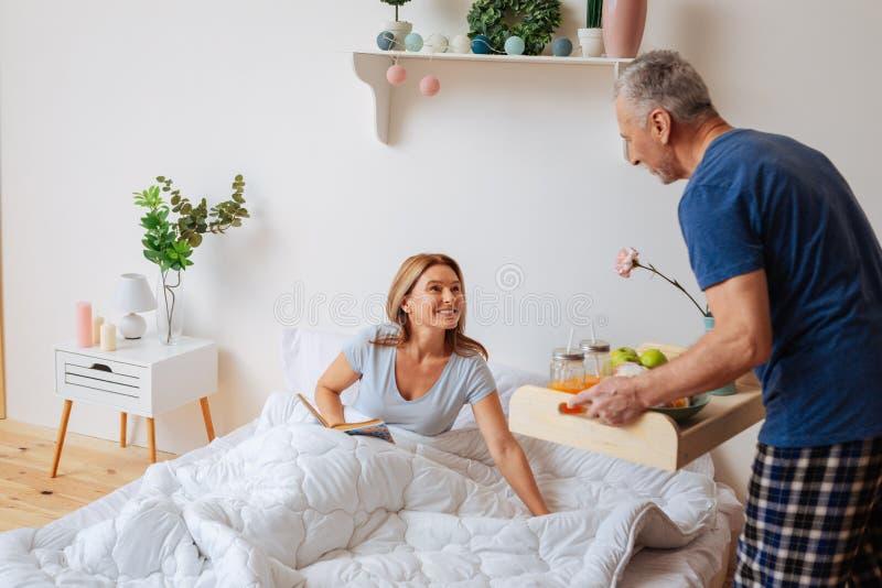 Esposa que come o café da manhã com o marido no quarto após a leitura imagens de stock royalty free