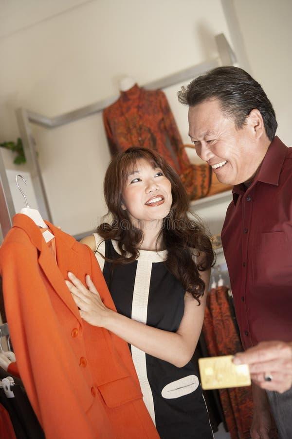 Esposa que mostra o marido, com cartão de crédito, revestimento foto de stock