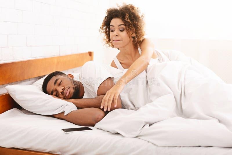 Esposa sospechosa que comprueba su teléfono móvil del marido el dormir en cama fotografía de archivo