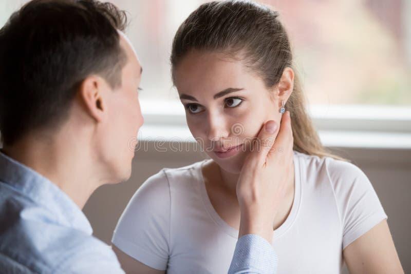 Esposa triste que mira al marido que toca la cara para calmar abajo fotografía de archivo