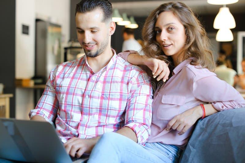Esposa y marido hermosos jovenes que usa el ordenador portátil en el café y practicando surf foto de archivo libre de regalías
