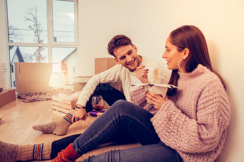 Esposa y marido que se sientan en el piso que cena primer en nuevo sitio fotos de archivo