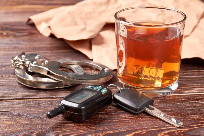 Esposas, llaves del coche, vidrio del whisky foto de archivo