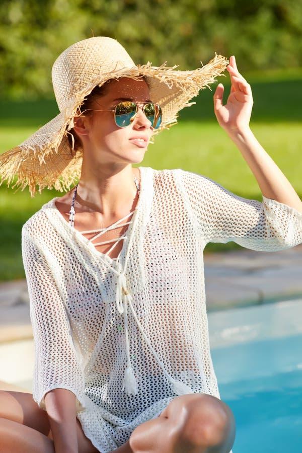 Esposizione al sole della giovane donna nella piscina della località di soggiorno di stazione termale fotografie stock libere da diritti