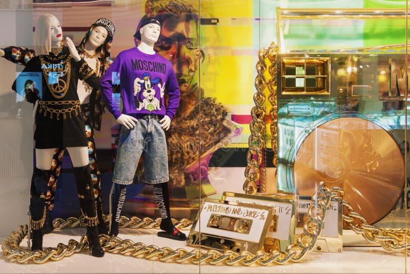 Esposizione brillante della finestra di deposito di H&M con la raccolta degli indumenti di Moschino fotografia stock libera da diritti
