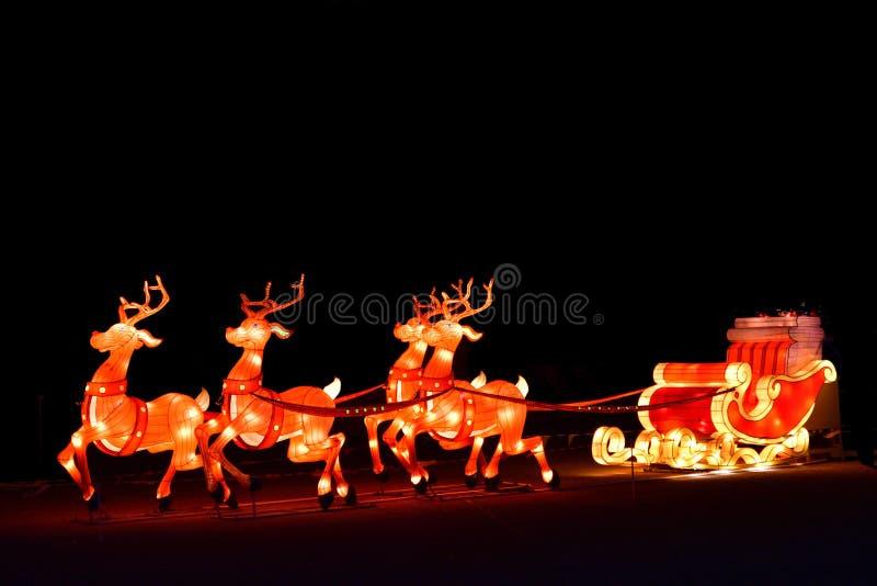 Esposizione decorativa delle luci di Natale di inverno del trasporto di Santa con la renna fotografia stock libera da diritti