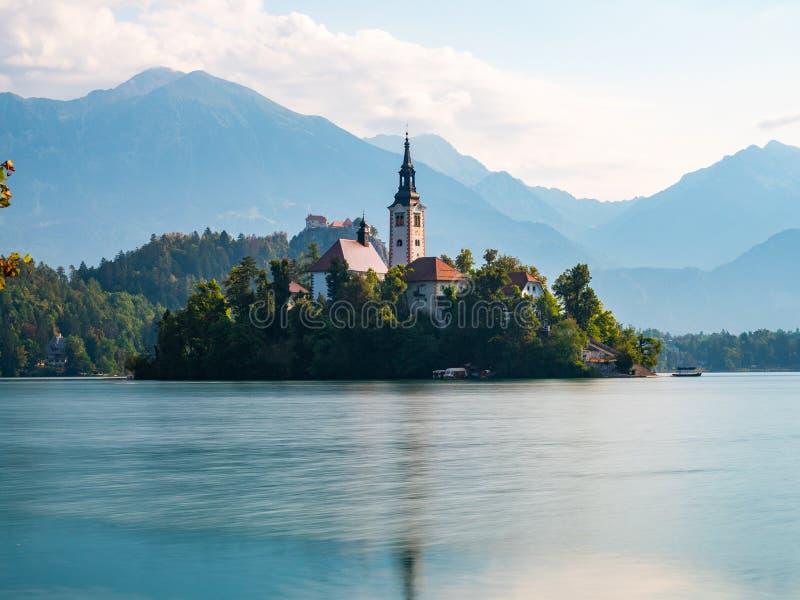 Esposizione lunga della Slovenia sanguinata lago, primo mattino, giorno nuvoloso, riflessioni nell'acqua fotografie stock libere da diritti
