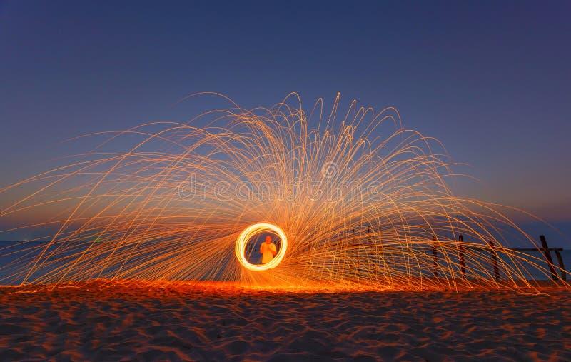 Esposizione lunga di lana d'acciaio bruciante che è filata in una sfera sopra fotografia stock libera da diritti
