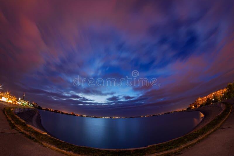 Esposizione lunga di scena urbana di notte con le nuvole sul cielo drammatico e immagini stock libere da diritti