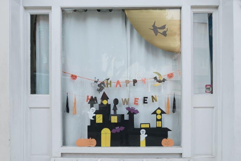 Esposizione sveglia dei mestieri di carta dei bambini alla finestra della casa della scuola materna per la celebrazione il 31 ott fotografie stock
