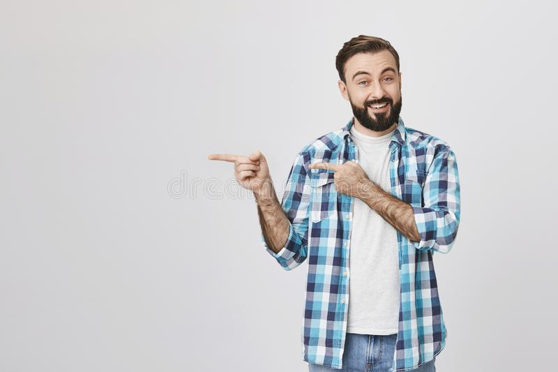 Esposo adulto considerável com a barba e o bigode, sorrindo e expressando o elogio ao apontar à esquerda com duas mãos imagem de stock royalty free