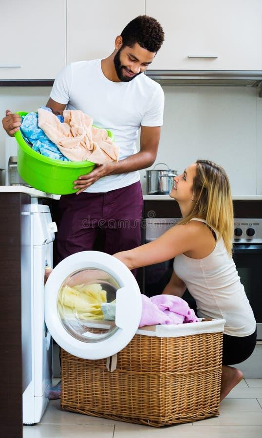 Esposos misturados que fazem a lavanderia regular fotografia de stock royalty free