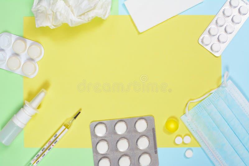 Espray nasal, pañuelos, termómetro, medicinas, máscara médica en el fondo azulverde con la ampolla grande Frío y gripe imagenes de archivo