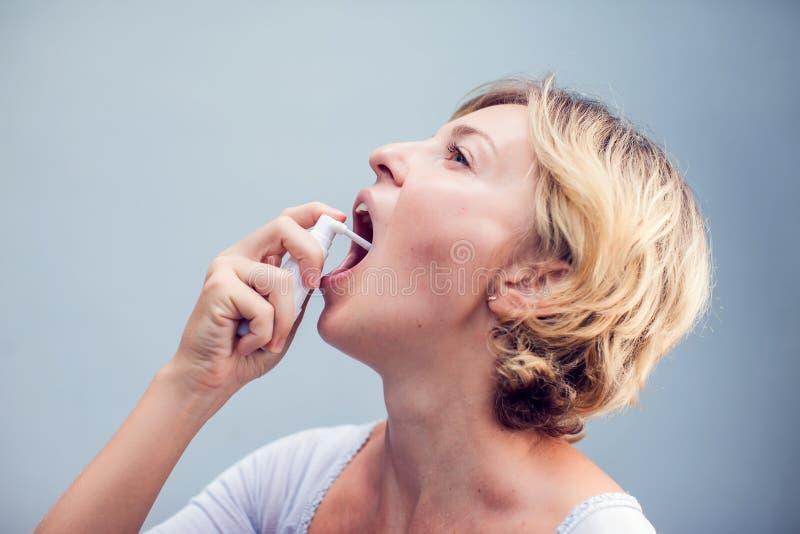 Espray para la garganta dolorida Foto de una mujer que trata sus wi de la garganta imagen de archivo