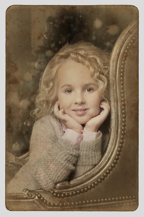 Espreitar de assento da menina loura pequena bonito sobre a cadeira arma-se imagens de stock royalty free
