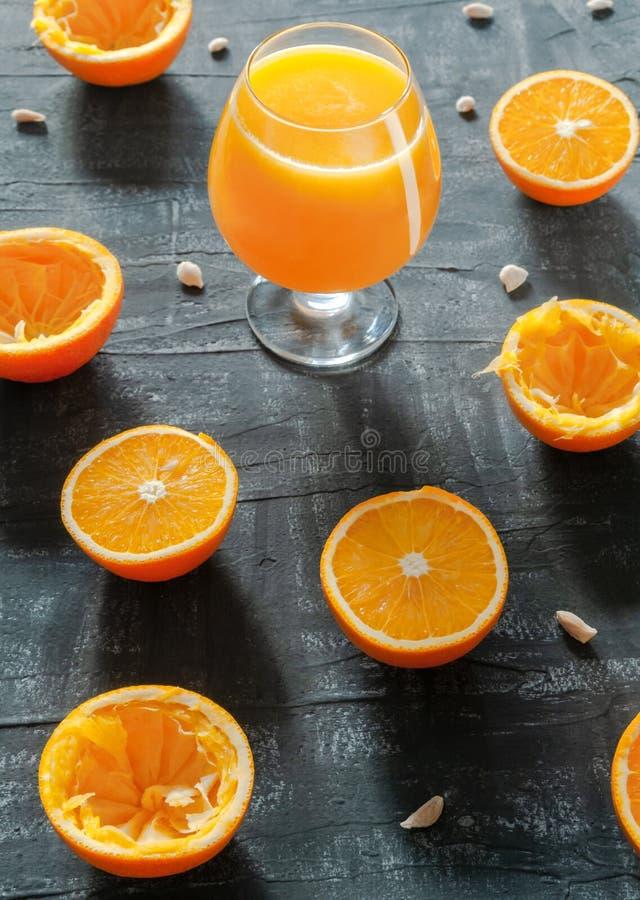 Espremeu recentemente o suco de laranja em um vidro para a aguardente Ao lado do vidro são as laranjas cortadas e o fundo escuro  imagens de stock royalty free