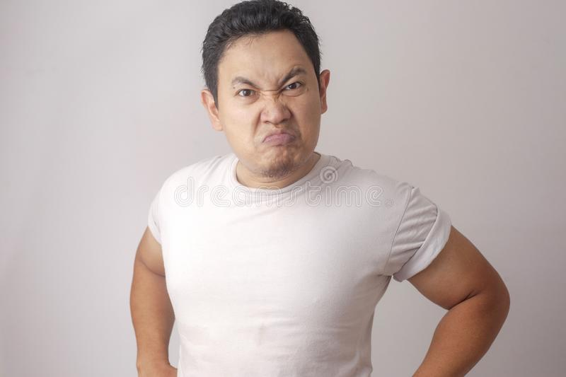 Espressione asiatica cinica arrabbiata dell'uomo immagine stock