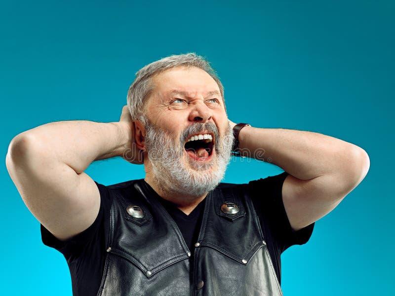 Espressione felice sorridente dell'uomo di mezza età che posa davanti ad un fondo blu con lo spazio della copia fotografia stock