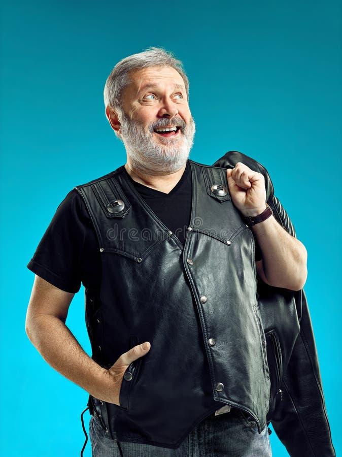 Espressione felice sorridente dell'uomo di mezza età che posa davanti ad un fondo blu con lo spazio della copia immagine stock