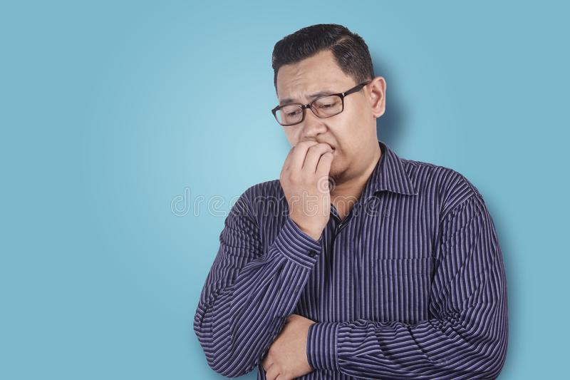 Espressione preoccupata o nervosa dell'uomo, unghie mordenti fotografia stock