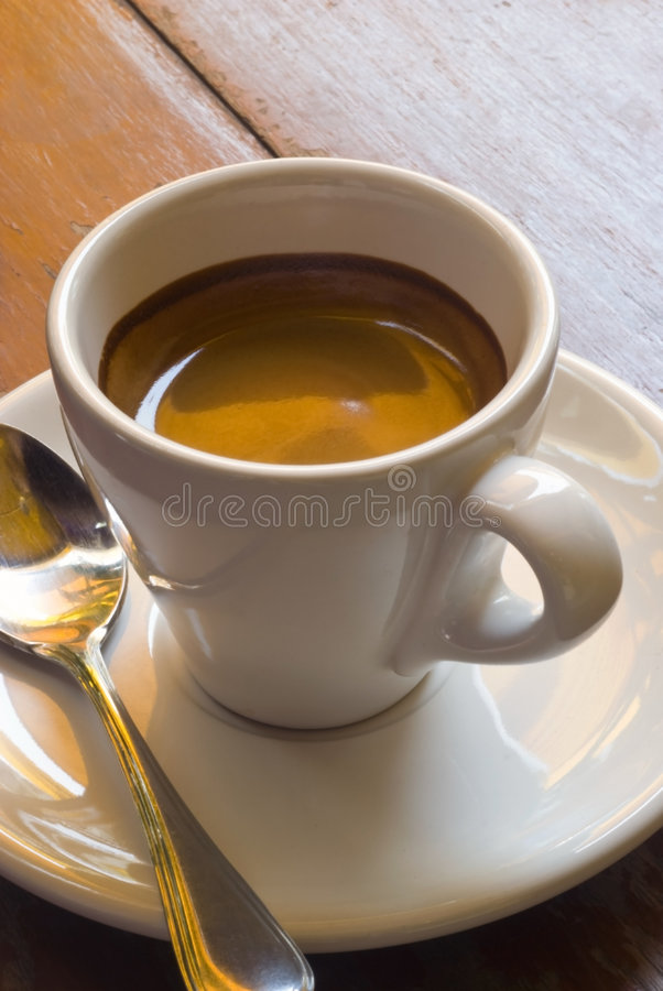 Espresso. A cup of espresso coffee on a wooden table royalty free stock photography