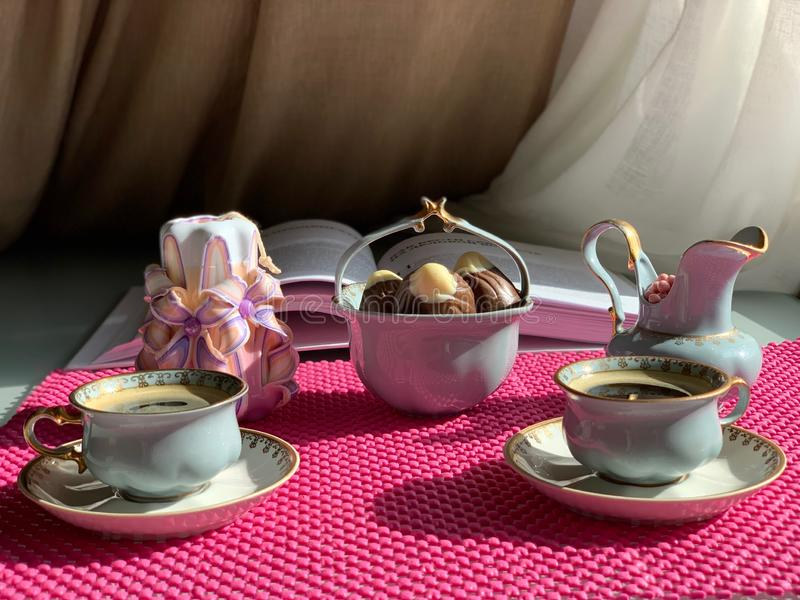 Espresso coffee in beautiful cups. Coffee set, sweets in a candy jar, beautiful pink drops, decorative candle royalty free stock photography