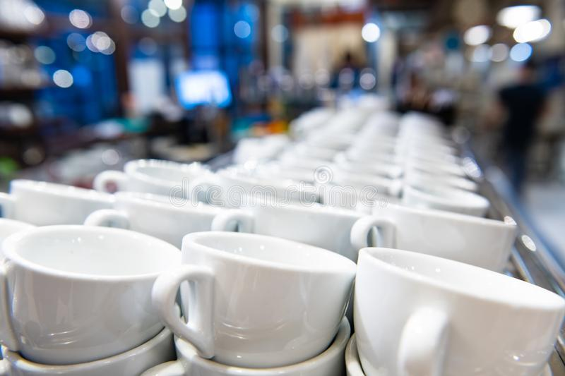 Espresso coffee cups row in coffee shop. Close up of white espresso coffee cups aligned in a row ready for use, selective focus with coffee shop atmosphere in royalty free stock images